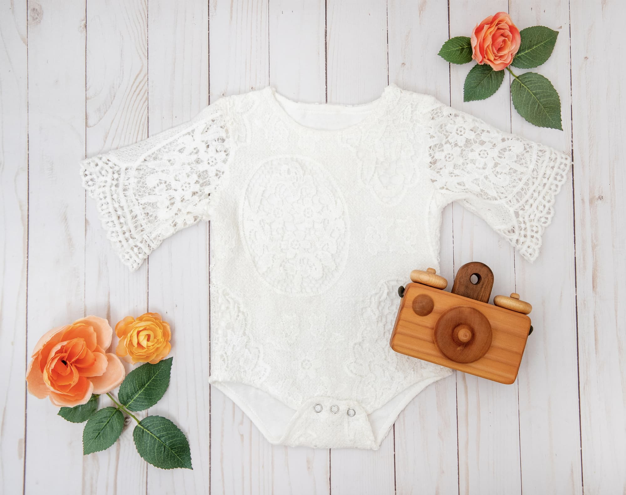 lace baby outfit flat lay with wooden camera