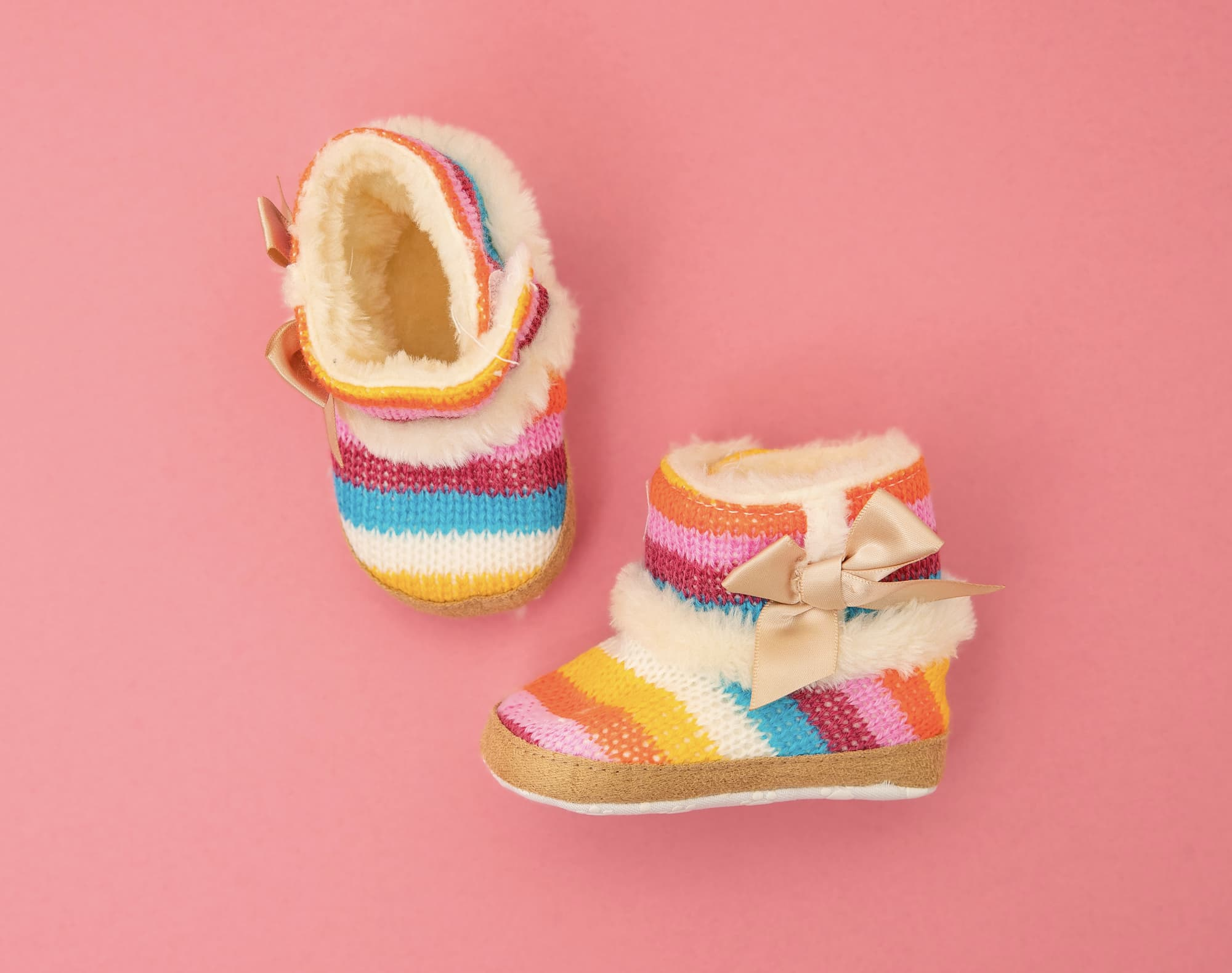 colorful baby shoes on pink background