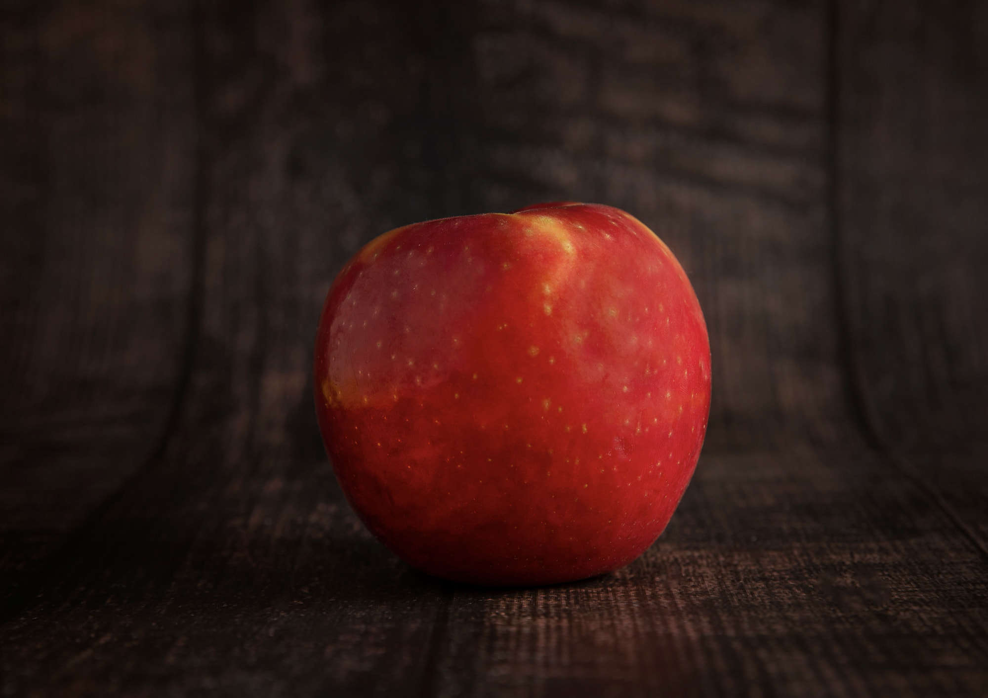 red apple on dark wooden table