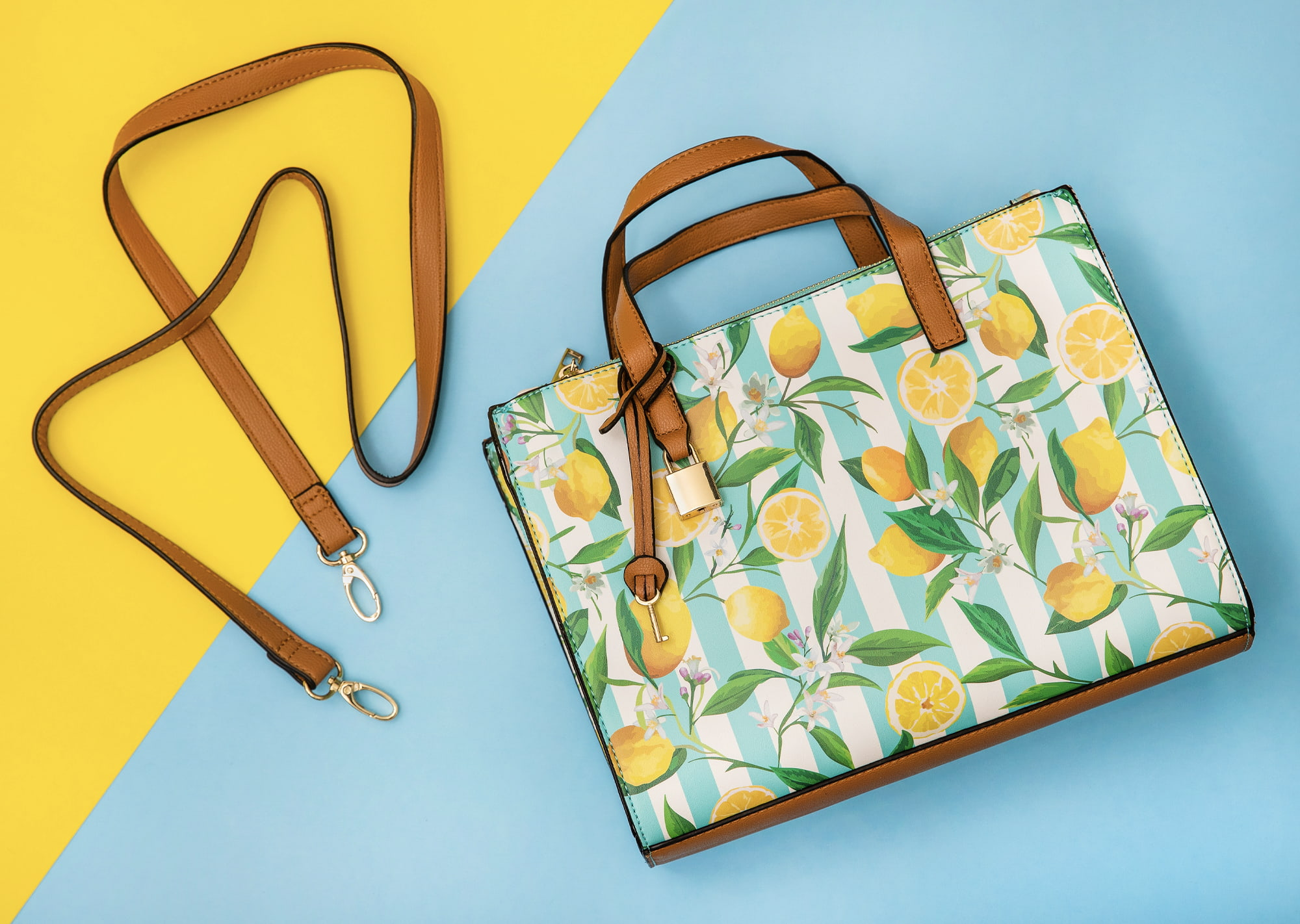 flat lay of lemon purse on yellow and blue background